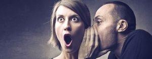 Man telling woman a secret who is shocked