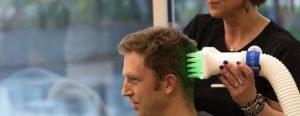 Technician performing heated air head lice treatment on man