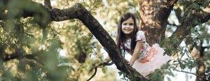 Little girl in pretty dress up in a tree