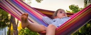 Little girl in a hammock on a beautiful day