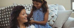 Girl looks through her moms hair